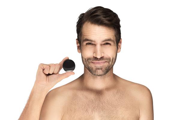 un hombre sonriendo con una coreo mini en la mano