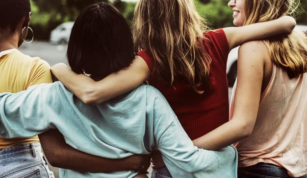 Vista trasera de un grupo de diversas amigas caminando juntas