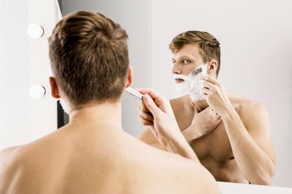 hombre afeitándose con cuchilla delante de un espejo