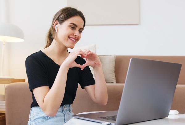 una chica frente a un ordenador formando un corazón con las manos