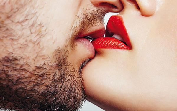 dos bocas, de hombre y mujer con los labios pintados, besándose