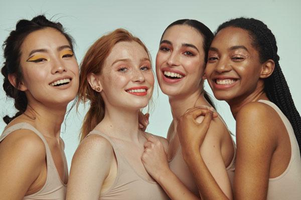4 chicas de razas diferentes sonriendo