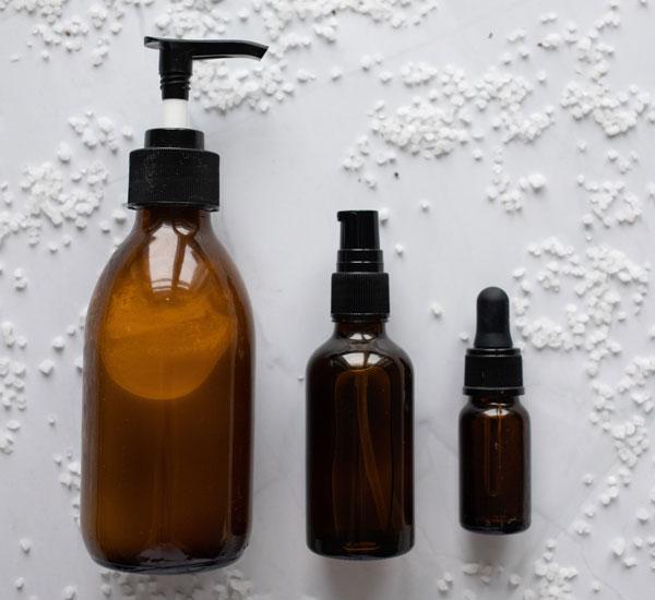 tres frascos genéricos de productos, de distinto tamaño, de color ámbar