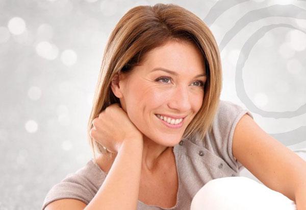 una mujer con aspecto sonriente apoyada sobre su mano derecha