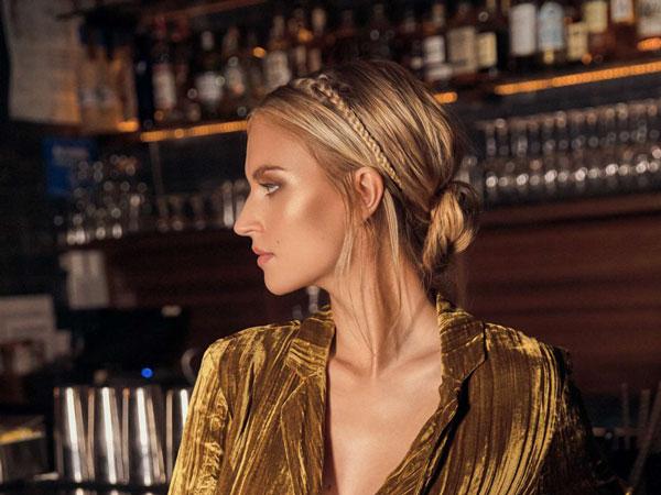 Chica rubia peinada con un moño bajo y vestida de fiesta apoyada en la barra de un bar